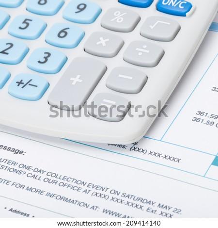 Receipt next to calculator - studio shot - 1 to 1 ratio - stock photo