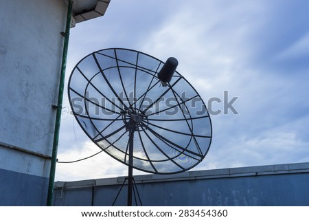 Receive satellite dish on top of building in sunset. Silhouette - stock photo