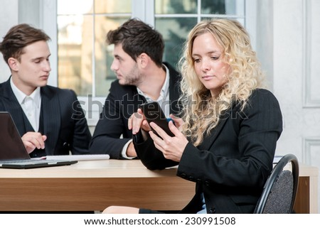 Receiving a call. Businesswoman looking at cell phone while his colleague businessmen talking in the background sitting at table - stock photo