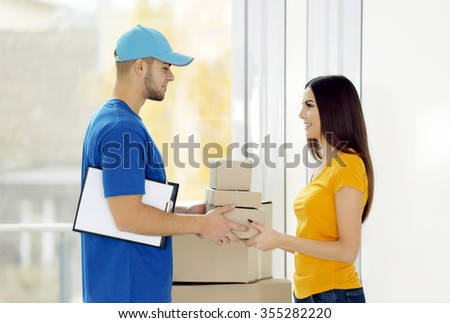 Receiving parcel - delivery man gives package to young woman - stock photo
