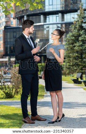 Recent business news. Two business colleagues are discussing las business news and smiling, while standing with tablet