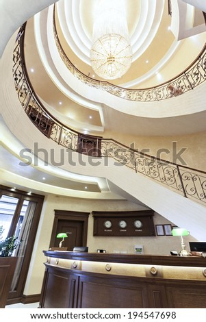 Reception area with reception desk and luxury spiral stairs - stock photo