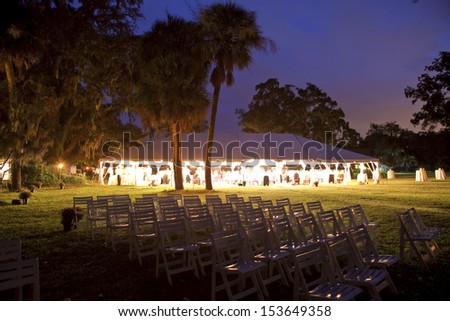 reception tent surrounded by trees, lit up at night - stock photo