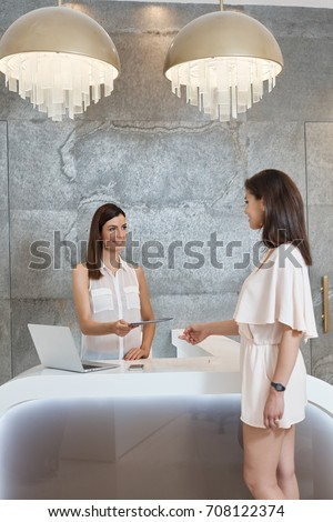 Receptionist and guest at elegant salon.