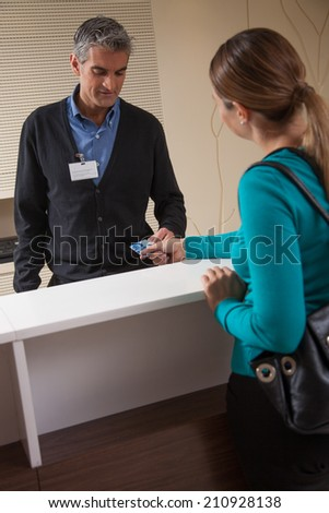 Receptionist and patient discussing about payment at reception desk in hospital. - stock photo