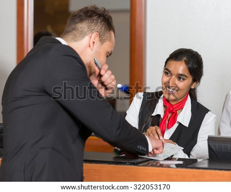 Receptionist at hotel reception assisting a guest with city map - stock photo