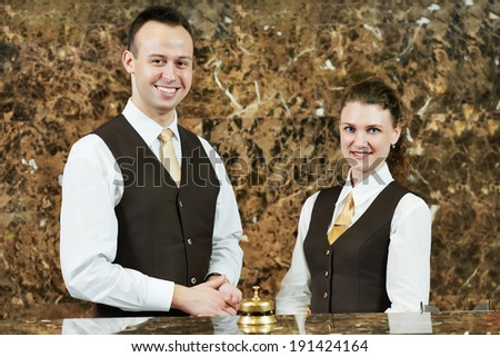 Receptionist or concierge workers standing at hotel counter - stock photo