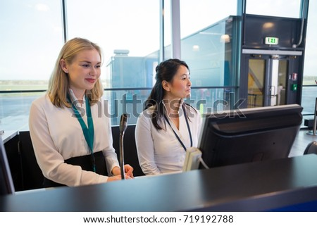 Receptionists Sitting At Help Desk In Airport