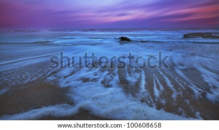 Recessing tide and sunset over sandy ocean beach - stock photo