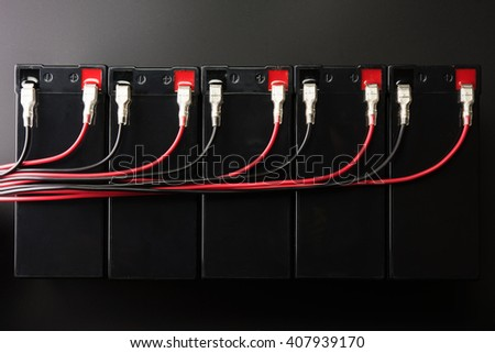 Rechargeable batteries, and electrical wires. Industrial battery hooked up in parallel with long red and black cable bundles, coming from the terminal.  - stock photo
