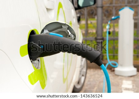 Recharging an electric car, an environment friendly alternative - stock photo