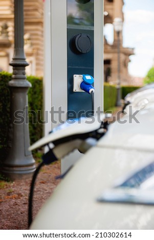 Recharging station with charging of an electric car - environmentally friendly concept - stock photo