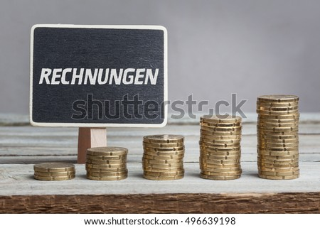 Rechnungen (invoices) in German language, white chalk type on black board, Euro money coin stacks of growth on wood table.