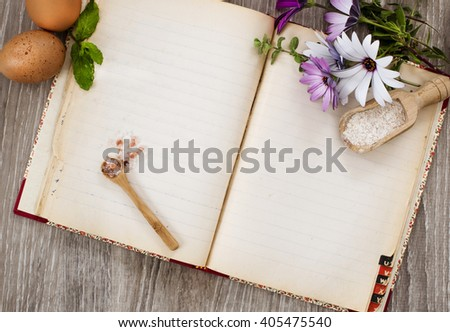 recipe book and raw food ingredients over wood