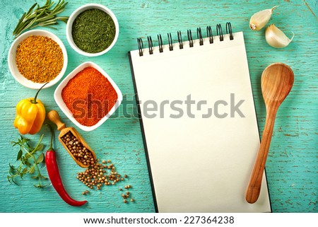Recipe book and various spices on blue wooden background - stock photo