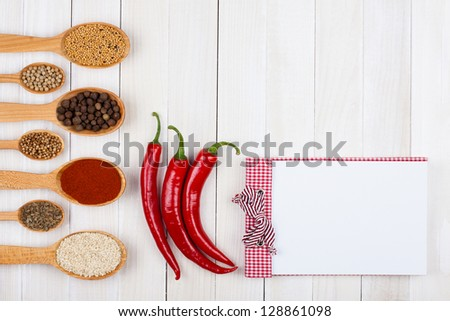 Recipe book, chili pepper, spices in spoons  on white wood background