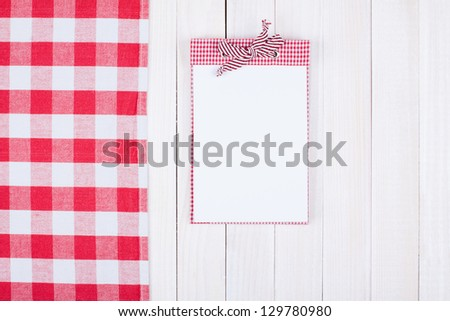 Recipe book, kitchen tablecloth on white wood background - stock photo
