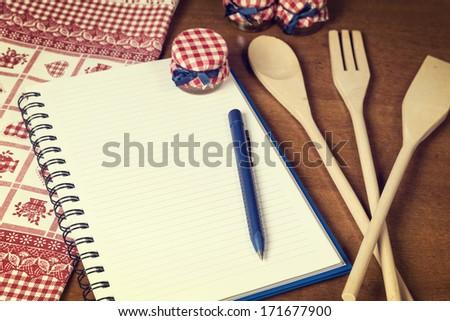 Recipe book on kitchen table. - stock photo