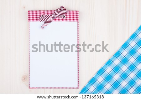 Recipe cook book, blue tablecloth on wood background - stock photo