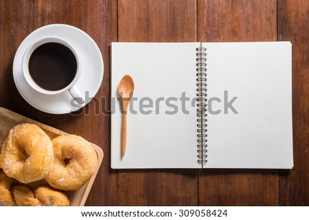 Recipe notebook, donuts, Coffee cup top view on wooden table