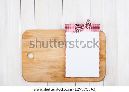 Recipe notebook, kitchen plank on white wood background - stock photo