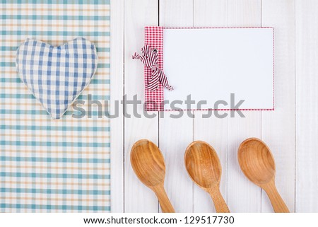 Recipe notebook, tablecloth, heart, spoons on white wood background