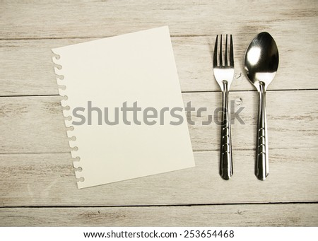 Recipe paper and Spoon and fork on white wooden table. - stock photo