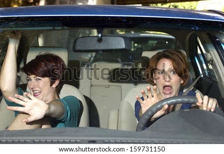 reckless driver and scared female passenger in a car - stock photo