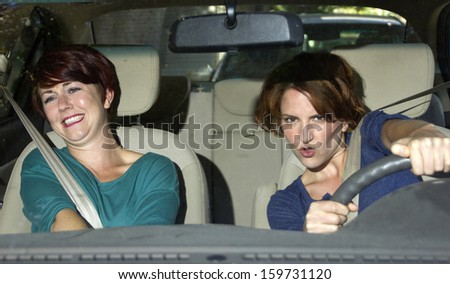 reckless driver and scared female passenger inside a car - stock photo