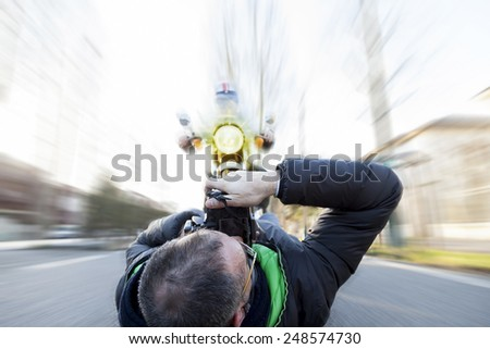 reckless photographer shooting a motorcyclist  - stock photo