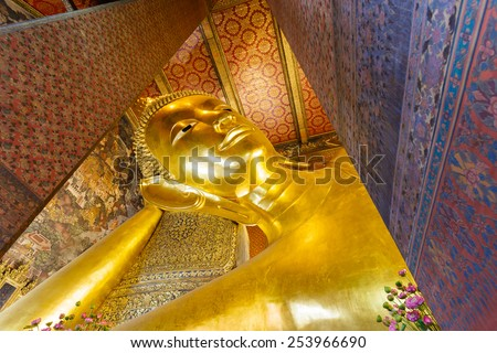 Reclining Buddha gold statue face - stock photo
