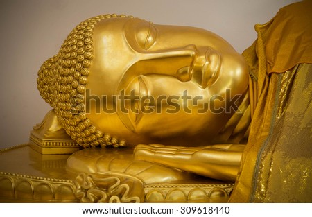 Reclining Buddha gold statue face close up - stock photo