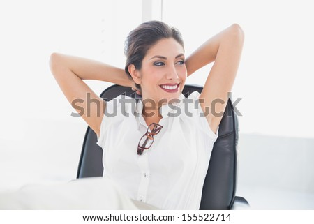 Reclining businesswoman sitting at her desk smiling in her office - stock photo