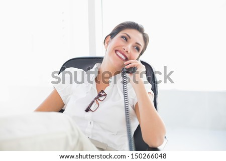 Reclining businesswoman sitting at her desk talking on phone in her office - stock photo