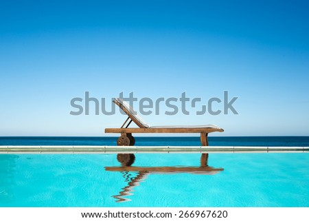Reclining chair near a swimming pool, sea and blue sky background - stock photo