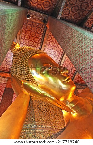 Reclining golden Buddha in Thailand - stock photo