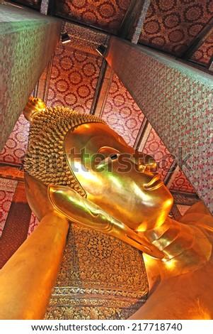 Reclining golden Buddha in Thailand - stock photo