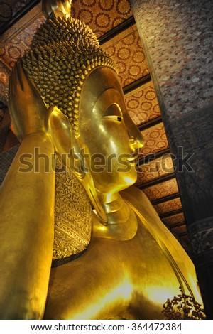 Reclining golden buddha inside the temple Wat Pho in Bangkok, Thailand. - stock photo