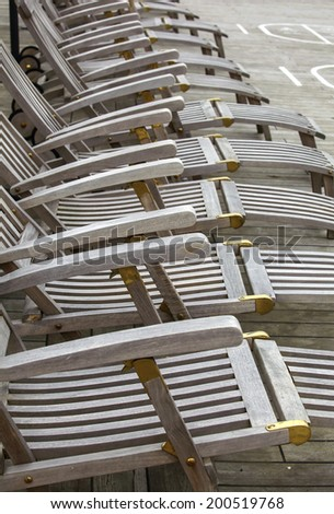 Reclining wooden deckchairs on a cruise ship - stock photo
