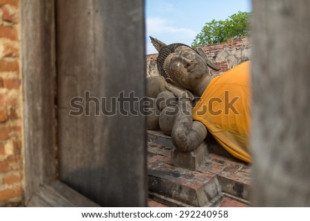 Reclinning Buddha against blue sky looking through a wooden window frame in Ayuthaya province (Ancient City), Thailand - stock photo