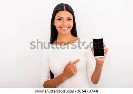 Recommending you this smart phone. Smiling young woman holding mobile phone and pointing at it while standing against white background - stock photo