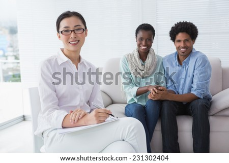Reconciled couple smiling at camera with therapist in therapists office - stock photo