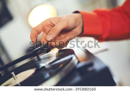 Record player spinning the disc with music. Hand putting needle on vinyl - stock photo
