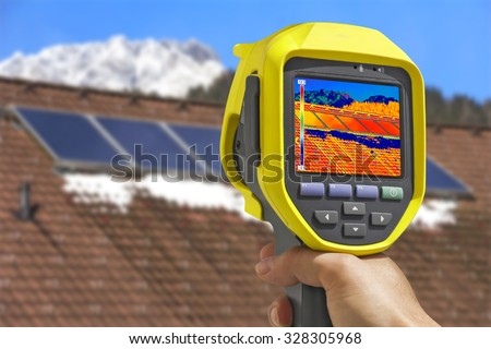 Recording Photovoltaic Solar Panels on the roof House With Thermal Camera  - stock photo