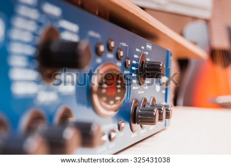 recording studio gears & acoustic guitar on background, focus to knob & shallow dept of field for studio music recording concept - stock photo