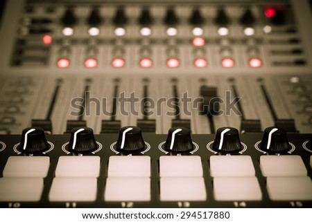 recording studio gears ,broadcasting tools, mixer, synthesizer focus to knobs. shallow dept of field for music background - stock photo