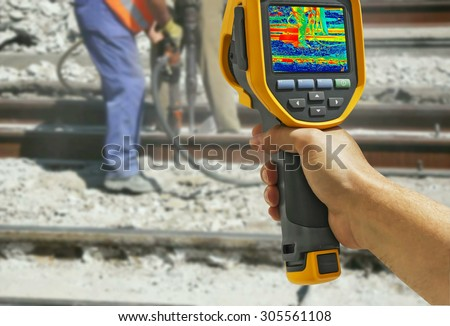Recording with Infrared camera Two Workers with pneumatic hammer breaking Concrete at construction site - stock photo