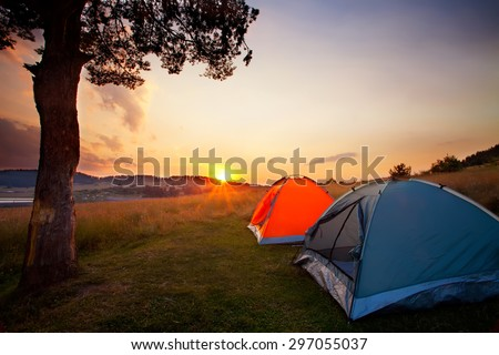 recreation area and camp with tent, sunset time with rising sun near high mountain lake
