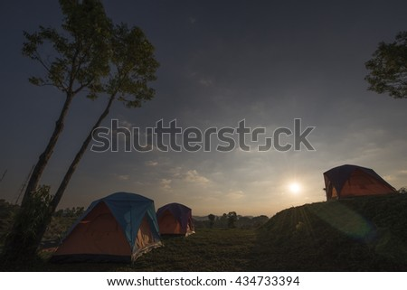 recreation area and camp with tent, sunset time with rising sun near high mountain.with low light feeling.