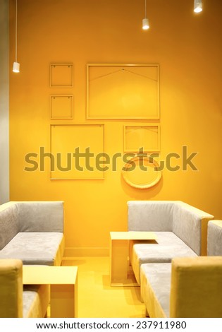 Recreation area. Fragment of interior loft. Part of the lobby with sofas and yellow decorative empty frame on the wall. Lounge zone. - stock photo